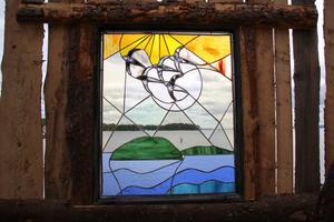 Ingång till Dellen heter Karl Arne Ytterströms stuga med färgat glas mot Dellens vågor, av MAts Nord.