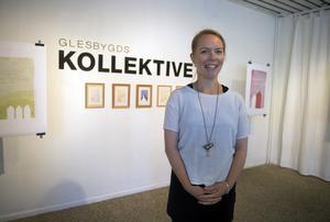 Tove Gulliksson. I bakgrunden hänger de små originalmålningarna som sedan har tryckts upp i större affischer.
