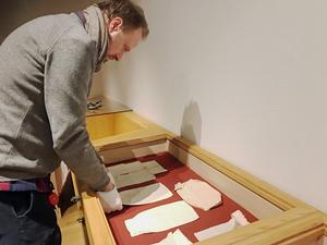 Carl Anders Skoglund på Hälsinglands museum placerar så kallade nattkappor (lösa kragar och halvärmar) i en monter, i den nya textila utställningen om linneplagg.