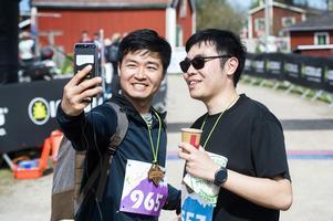 Cheuk Hei Tong, nummer 557 till höger, tar en bild med sin löparkamrat efter målgången.