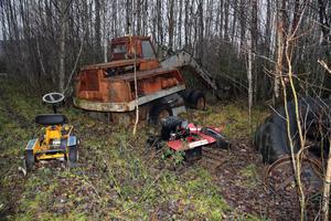 På den här platsen har man dumpat en grävare och en åkgräsklippare  samt annat skrot.