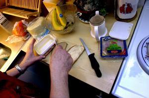 Äldreomsorgspersonal brer en smörgås. Foto: Janerik Henriksson/TT
