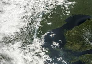 En satellitbild över Mellansverige, tagen tisdag 5/8. I mitten av bilden syns rökplymen från skogsbranden otydligt genom molnen precis vid gränsen till det molnfria området vid Bottniska viken. Skogsbranden, den största i Sverige i modern tid, har hittills krävt ett liv.