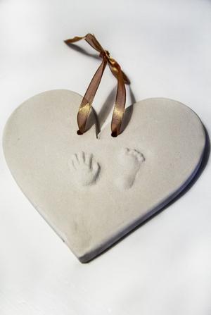 Neos fot- och handavtryck finns avgjuten i ett hjärta i hemmet. Både fot och hand är bara några centimeter långa.