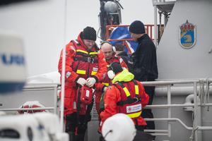 Två personer på lotsbåten bedöms vara skadade och behöver vård. Sjöräddningssällskapet från Hudiksvall får i uppgift att hämta en av dessa och ta till land.