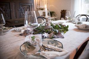 I matsalen dukas det till jul med vackert porslin, linne och levande ljus. Servetterna är gjorda av gamla örngott.