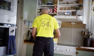 Janne kokar kaffe och bär tröjan från fjolårets Lidingölopp.