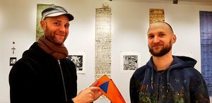 """I montrarna på utställningen blandar Sebastian och Christoph Mügge saker från olika tidsperioder. De berättar att triangeln på orange bakgrund är internationell symbol, inte bara svensk. De berättar också om hur viktigt det är att ha kontanter i händelse av krig: """"I Sverige försöker man nästan avskaffa kontanter, medan man i Tyskland värdesätter kontanter. Vad händer om bankomaten slutar fungera""""?"""
