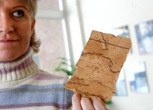 Ulrica Carlson med en bit plastmatta som innehåller asbest.