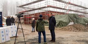Kommunchef Hannu Högberg ser positivt på att det nu byggs tio nya bostadsrätter i Norberg. Här intervjuas han av SVT medan ytterväggarna sätts på plats i bakgrunden.