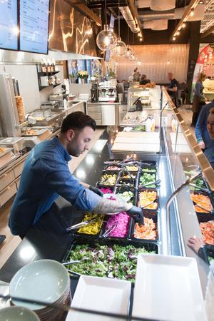 Ägaren Stefan Nas hjälper en kund som kombinerat sin egen kebab. Bakom honom syns en av två kebabrobotar.
