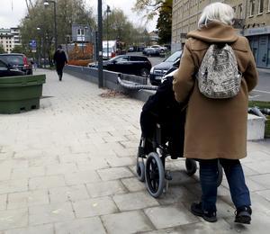 En kvinna i rullstol får hjälp av sin personliga assistent.