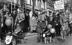1934 04 08. En barnvagnsparad med barn i uniform drar genom Berlins gator påhejade av äldre nazister. Foto: PRESSENS BILD