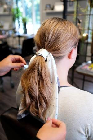 Victoria demonstrerar en frisyr som är trendig just nu, en tofs med scarf.