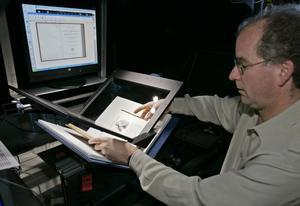 Internet Archives grundare Brewster Kahle visar hur den digitala inskanningen av böcker går till.  Foto: AP/Ben Margot