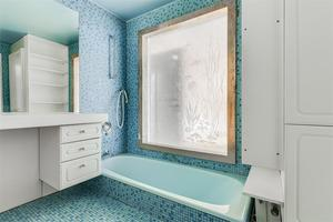 Badrummet har turkos mosaik, ett nedsänkt badkar och en vacker glasskiva som ger extra ljusinsläpp.