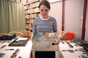 Emma håller i en av Anders Zorns paletter.