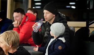 Tobias Eriksson, tillsammans med sitt barn, iakttog det hela från läktaren. Till vänster syns även Alexander Blomqvist i rött.