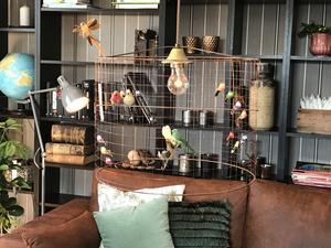 Många lampor har garn lindat på stommen, eller som här fåglar i olika material ovanför vardagsrumsbordet.
