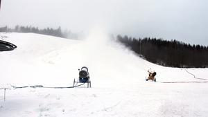 Snökanonerna gjuter snö på det stora hoppet i nedre delen av backen.