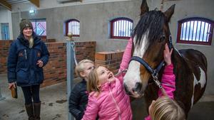 Alva klappar om ridskolehästen Twister som ridläraren Isabel Dahlström just ska förbereda för en lektion.