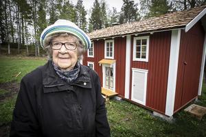 Stina Eliasson framför Stinastugan. På gaveln finns en dörr så en vuxen eller en rullstolsburen besökare kan få ta del av inredningen.