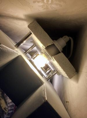 Hela klabbet fotograferat uppifrån. En lågenergilampa bakom varje bokstav. Långa skruvar går igenom plankan, förbi lamporna och in i bokstäverna. Ett litet metallrör döljer de fula skruvgängorna.
