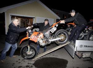 Torbjörn Maranders motorcykel ska lastas, och med hjälp av Christer Moberg och Magnus Stillmark. Daniel Myrgren avvaktar i bakgrunden.