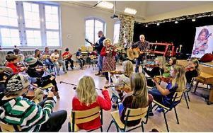 Hela gänget spelar musik. Projektledaren Eiwor Kjellberg står i mitten av ringen och spelar fiol. Foto: Johnny Fredborg