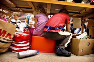 Carola Östbergs barn kryper under hennes bord.
