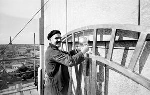 Hög höjd på jobbet. En arbetare monterar  en guldfärgad kula i stadshustornets klocka år 1960. Vet du mer?