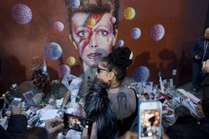 Fans till David Bowie sörjer artisten, både analogt och med hjälp av sina mobiler, vid en muralmålning i Brixton i London. Arkivbild.