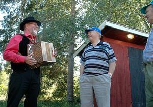 DURSPEL. Jalle Sjölund, Åland, förklarar skillnaden på ett durspel och ett dragspel för besökarna Börje Jansson och Sven Persson.