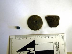 Fynd från järnåldersgraven; en glaspärla, en sländtrissa av sten och en ornerad keramikskärva från en bägare.