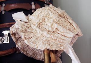 En huvudbonad till ett barn i krämvit siden med en vit rosett upptill, troligen från 1860-talet.