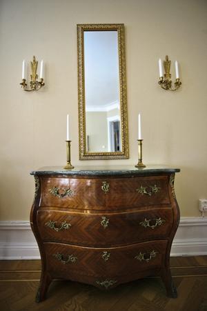 Rokokobyrån med marmorskiva är svensktillverkad. Claes ropade in den på en auktion i Hallsberg för 1000 kronor. Lampetterna kostade 50 kronor på loppis. Men spegeln köptes nytillverkad eftersom det visat sig svårt att hitta en gammal med klart glas.