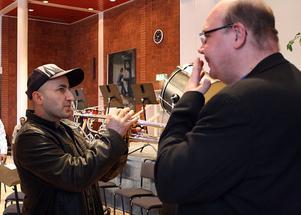 Musikläraren Mats Siggstedt visar Falah hur man får ljud i en trumpet.
