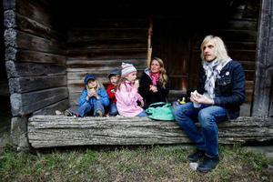 """Edvin, Arvid och Alva Bydén sitter och fikar med sina föräldrar Lina Runudde-Bydén och Magnus Bydén. Edvin gillar Jamtli. Här får han prova på hur det var """"förr i tiden"""". Till exempel att använda svarta tavlan. """"Man skulle rita på någon tavla med krita"""", säger han."""