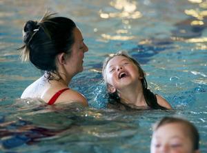 Lea Åsell skrattar högt av förtjusning över att flyta runt i bassängen med mamma Hilda.