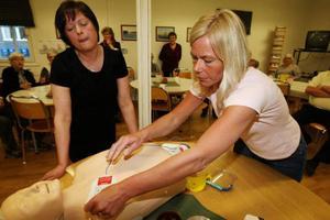 Ingela och Irja visar hur en hjärtstartare fungerar i praktiken.
