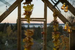 Ett växthus med en magisk utsikt att vila ögonen på. Den här kvällen sent i oktober är himlen rosa och bergen och Siljan djupt blå.