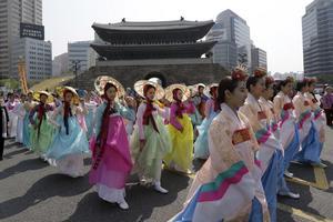 Kvinnor i traditionell sydkoreansk dräkt framför porten Sungnyemun.
