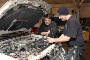 Robert Nordell och Peter Håberg tittar på en trasig motordel som förorsakat ett motorhaveri.