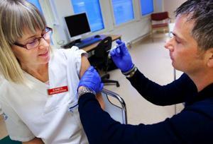 Undersköterskan Elisabeth Eriksson på akutmottagningen på Östersunds sjukhus var en av de första som vaccinerade sig mot den så kallade svininfluensan i länet. Biträdande enhetschefen på akuten, Fredrik Paananen, håller i sprutan. Foto: Håkan Luthman