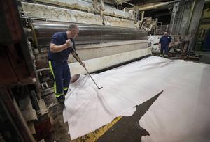 Mathias Wiklund, som hade tryckt på stoppknappen, städar ihop överblivet papper från den sista rullen. Längst bort syns Roger Zetterlund.