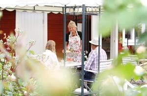 Birgitta serverar två stycken gäster.
