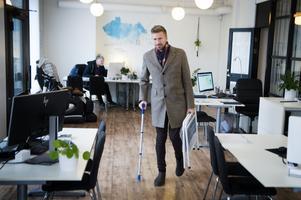 På kontoret i centrala Sundsvall trivs den förra hockeymålvakten bra. Här är han på väg ut, och efter operationen behöver han stundtals ha en krycka för avlastning fram till att styrkan är tillbaka.