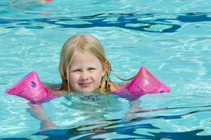 Lovisa Björnerud är fem år och har ännu inte lärt sig simma. Med hjälp av armpuffar tar hon sig ändå fram i den 50 meter långa bassängen.