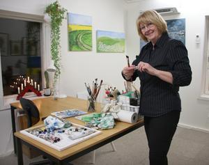 Marita förbereder lite färg innan hon sätter i gång och målar på en av sina halvfärdiga oljemålningar.