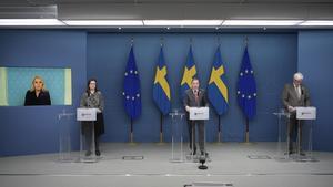 På podiet syns Anna Ekström, utbildningsminister, Stefan Löfven, statsminister och Johan Carlson, generaldirektör Folkhälsomyndigheten. På skärmen syns Lena Hallengren, socialminister.  Foto Anders Wiklund / TT